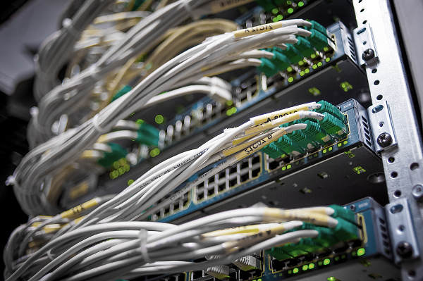 Netzwerkswitches in einem Rechenzentrum. ein WLAN-fähiger Router des Herstellers Linksys. Routing und Switching.